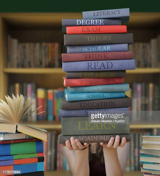 girl holding stacked books in library - book stock pictures, royalty-free photos & images