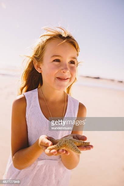 Girl holding starfish in hands