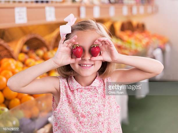 Fille tenant des fraises devant les yeux de l'épicerie
