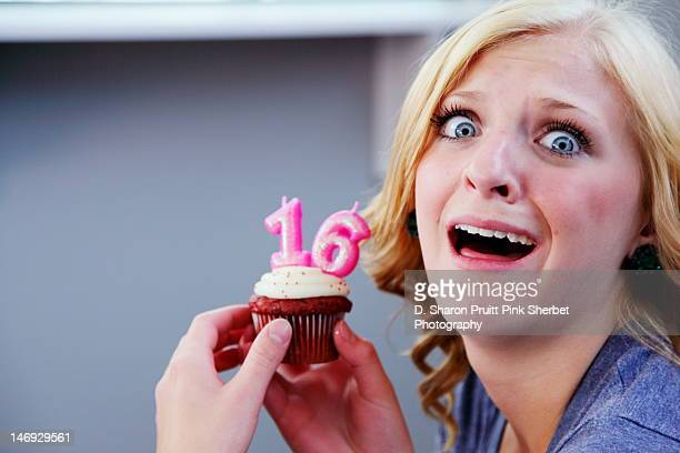 Girl holding sweet 16 birthday cupcake