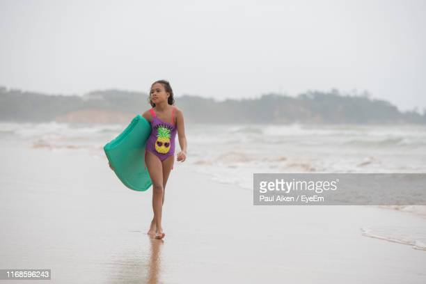 girl holding swimming float walking at beach - aikāne stock pictures, royalty-free photos & images