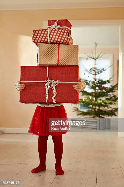 Girl holding tall stack of christmas presents
