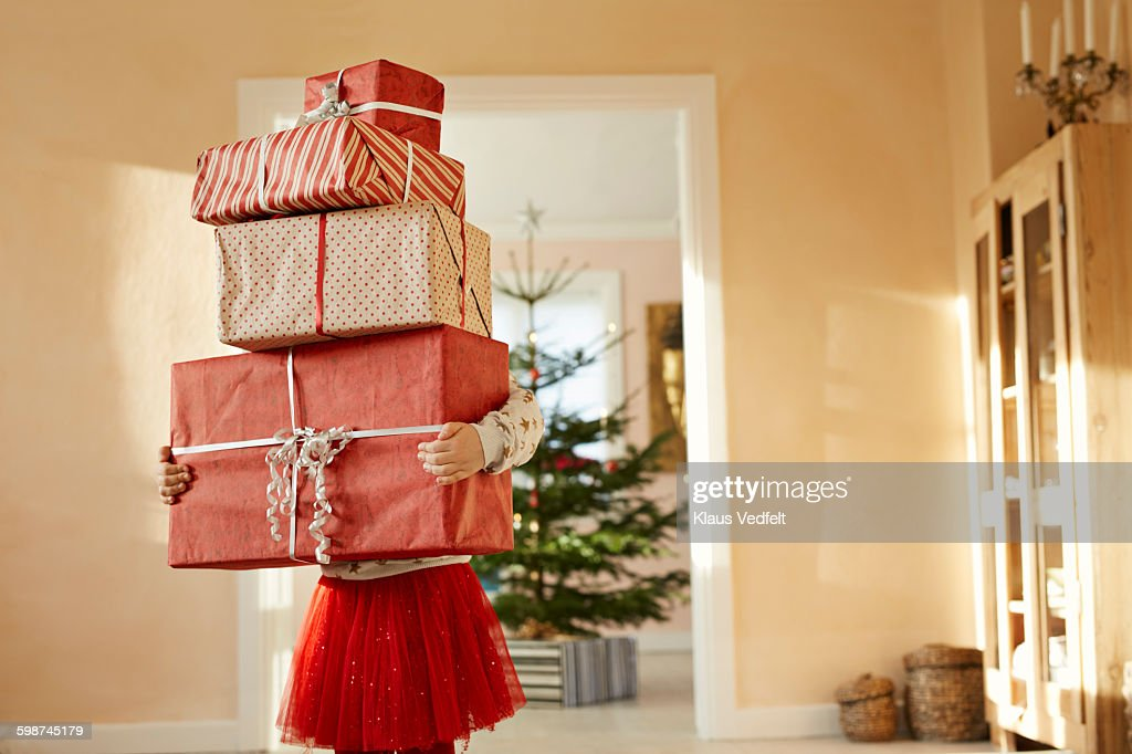 Girl holding tall stack of christmas presents : Stock Photo