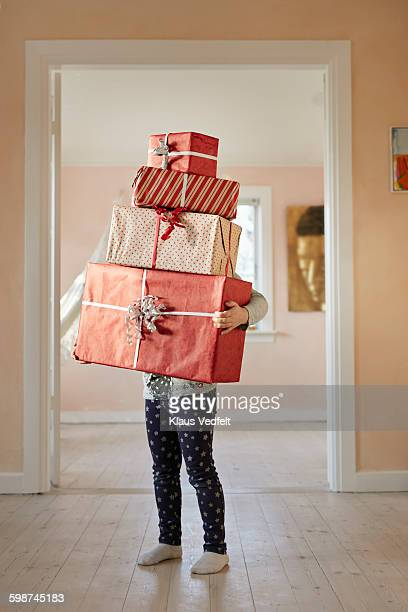 Girl holding tall stack of presents