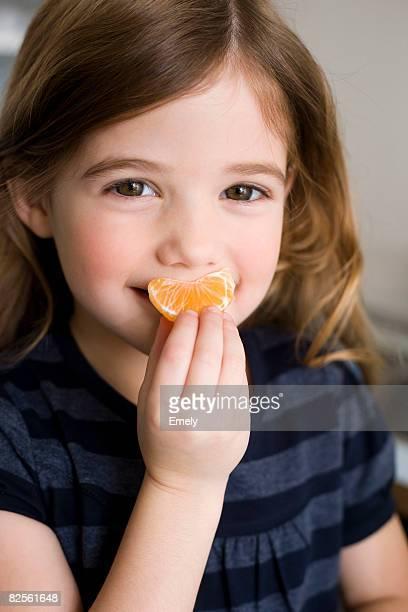 Girl holding tangerine
