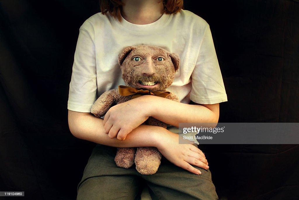 Girl holding teddy bear with freaky human face