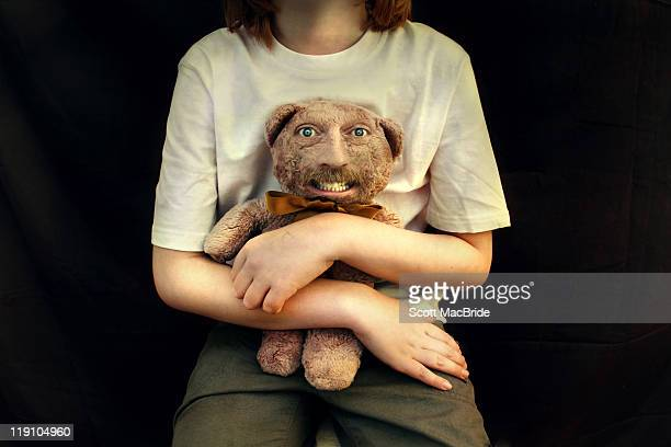 girl holding teddy bear with freaky human face - scott macbride stock pictures, royalty-free photos & images