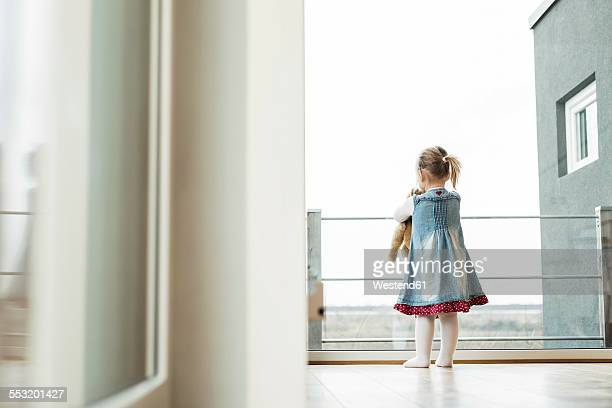 Girl holding teddy looking out of window