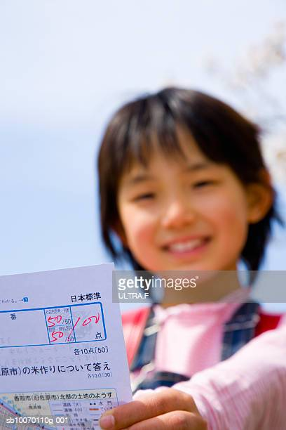 Girl (8-9) holding test of full marks