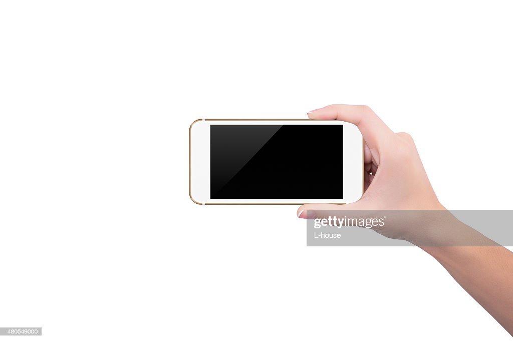 Girl holding the gold phone upright in her right hand : Stock Photo