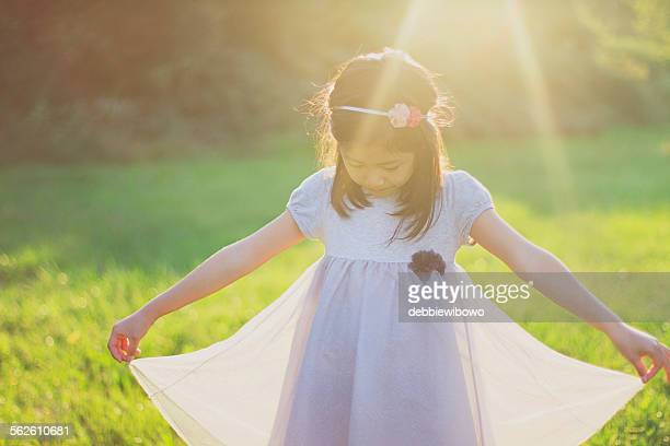 girl holding the hem of her dress - 裾 ストックフォトと画像
