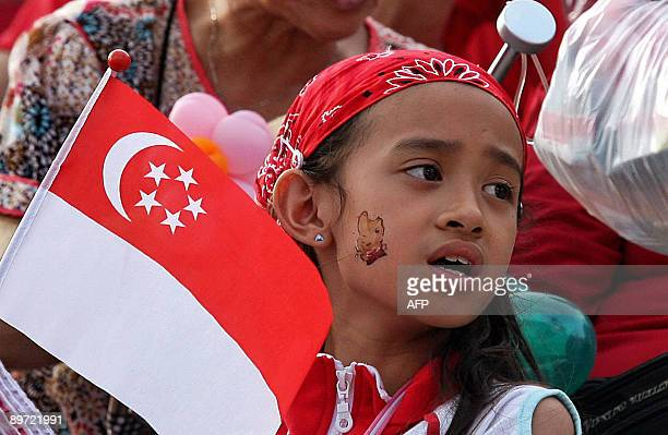A girl holding the Singapore flag sings along during an event to celebrate Singapore's 44th National Day on August 9 2009 In his National Day message...