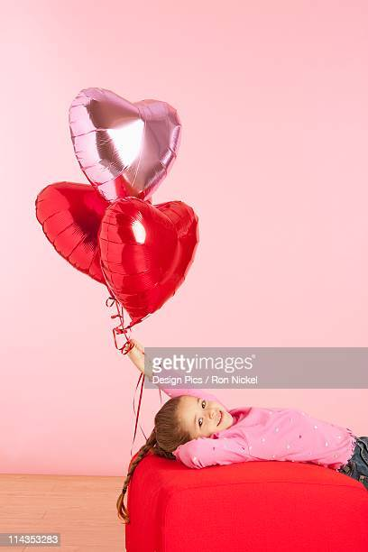 A Girl Holding Three Heart Shaped Balloons