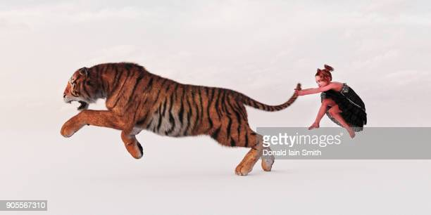Girl holding tiger by the tail