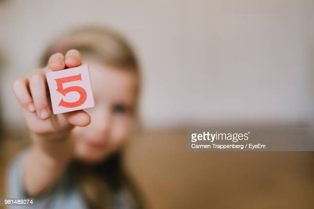 girl holding toy block while playing at home - number 5 stock pictures, royalty-free photos & images