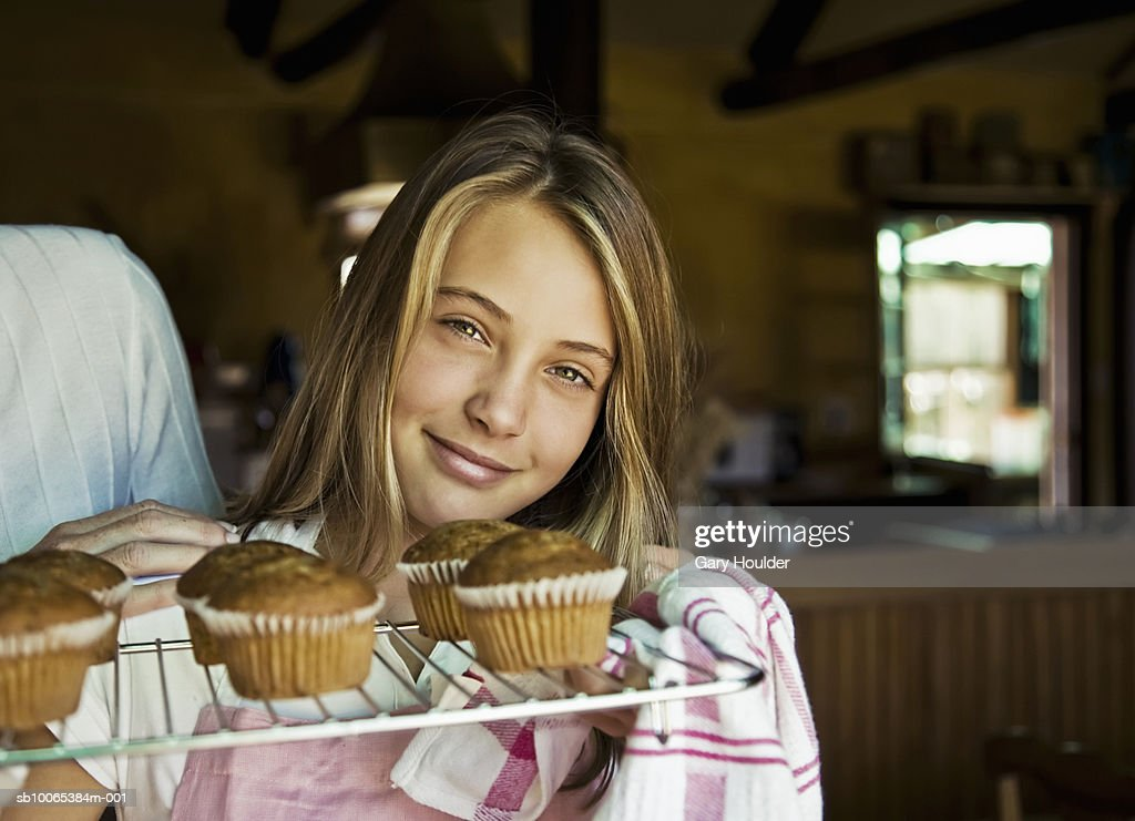 Girl (12-13) holding tray of baked cupcakes, portrait : Foto stock