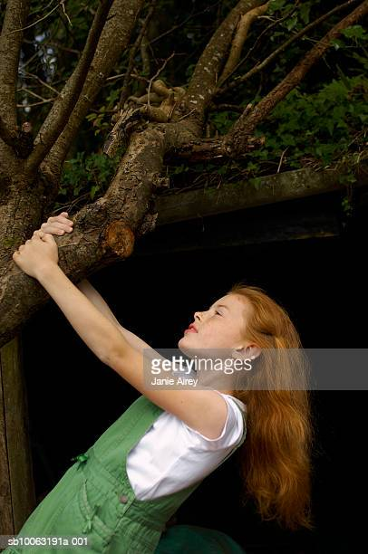 Girl (8-9) holding tree branch outdoors