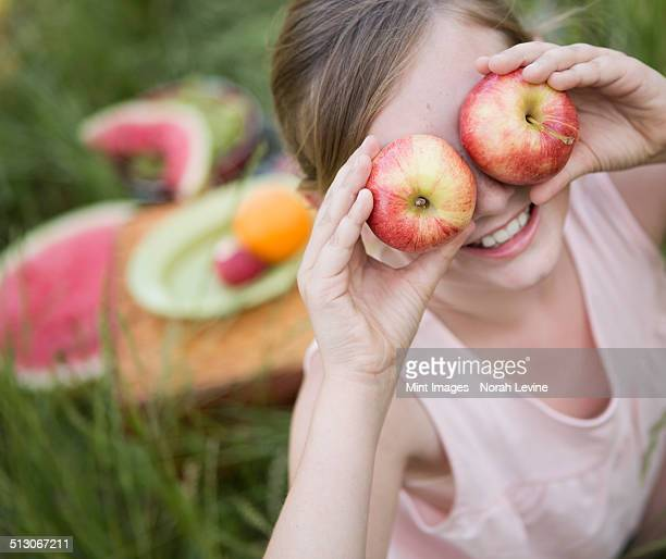 A girl holding two apples in front of her eyes