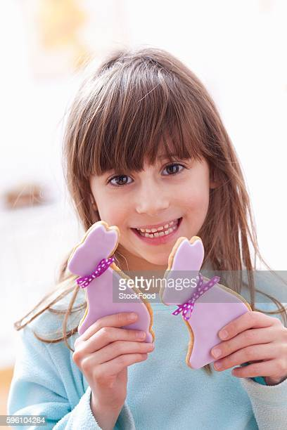 A girl holding two shortbread Easter bunnies