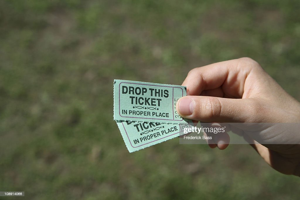 A girl holding two tickets, detail of hand : Stock Photo