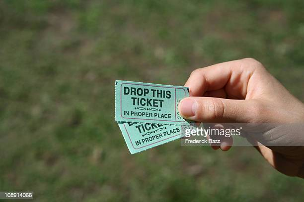 a girl holding two tickets, detail of hand - ticket stock pictures, royalty-free photos & images