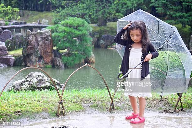 Girl holding umbrella in front of Japanese garden