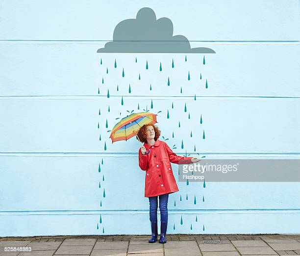 girl holding umbrella with cartoon rain cloud - weather stock pictures, royalty-free photos & images