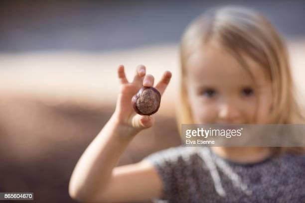 girl (4-5) holding up a conker - só uma menina - fotografias e filmes do acervo
