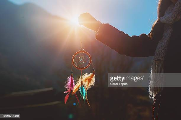 girl holding up a dream catcher on
