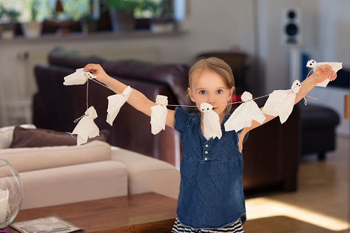 Girl (6-7) holding up a string of paper halloween ghosts - gettyimageskorea