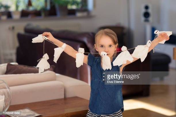 girl (6-7) holding up a string of paper halloween ghosts - halloween decoration stock pictures, royalty-free photos & images