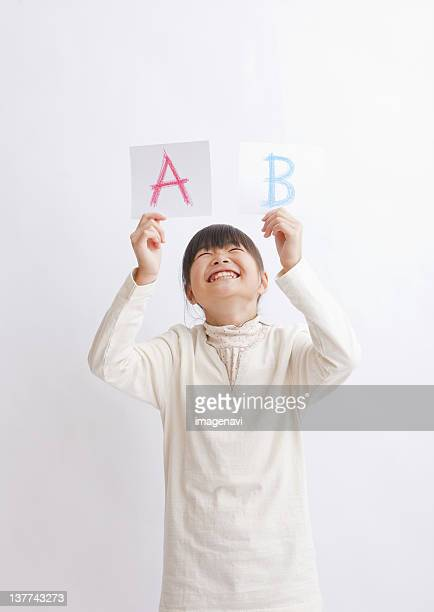 Girl holding up alphabet cards