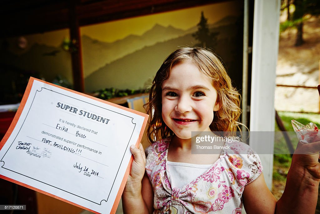 Smiling young girl holding up award after finishing summer camp