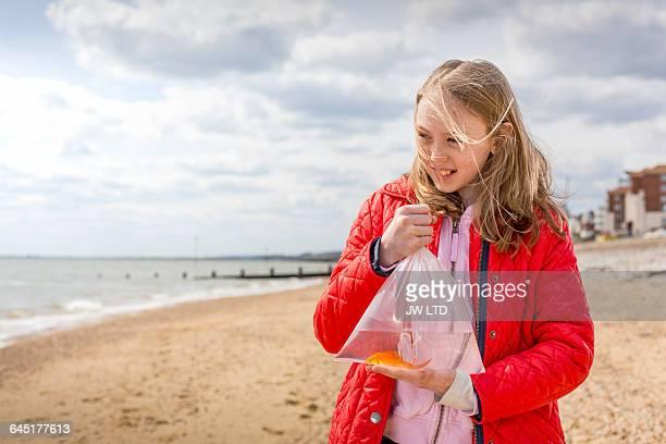 girl holding up clear plastic bag, Goldfish