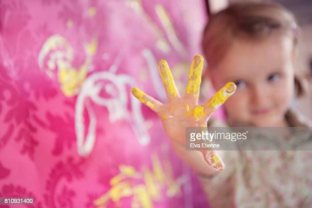 Girl holding up hand covered in finger paints, next to pink wallpaper