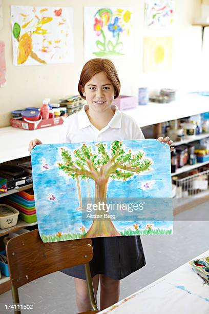 Girl holding up her painting