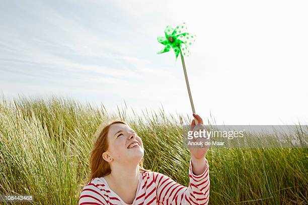 Girl holding up kids windmill in dunes