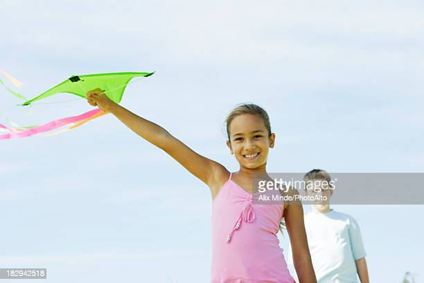 Girl holding up kite