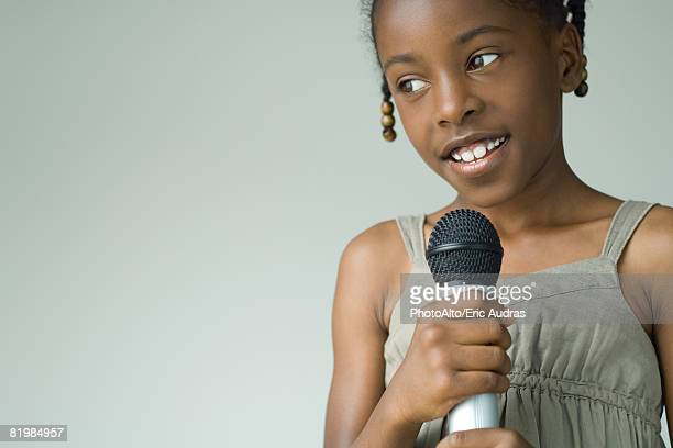 Girl holding up microphone, looking away, close-up