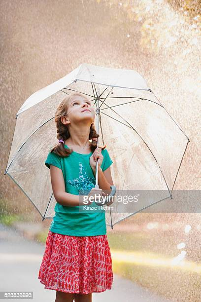 Girl holding up umbrella on rainy street