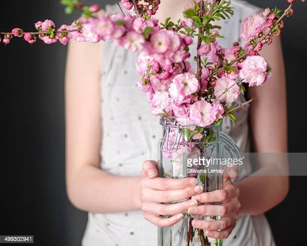 Girl holding vase of plum blossoms