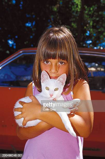 girl (12-13 years) holding white cat, outdoors - 12 13 years stock pictures, royalty-free photos & images
