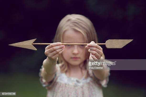 Girl holding wooden arrow