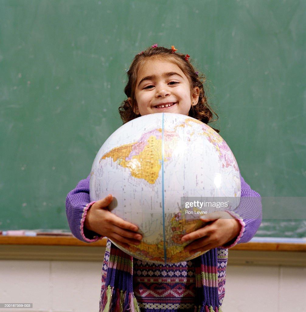 Girl (4-6) holding world globe, portrait : Stock Photo