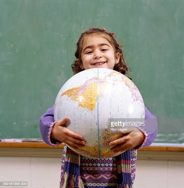 Girl (4-6) holding world globe, portrait