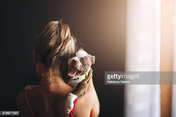 girl holding yawning Boston Terrier puppy