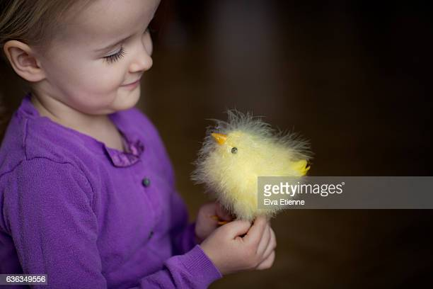 Girl (3-4) holding yellow Easter chick