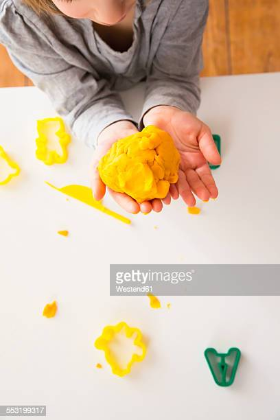 Girl holding yellow modeling clay in hands