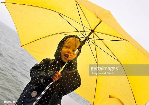 Girl holding yellow umbrella by lake