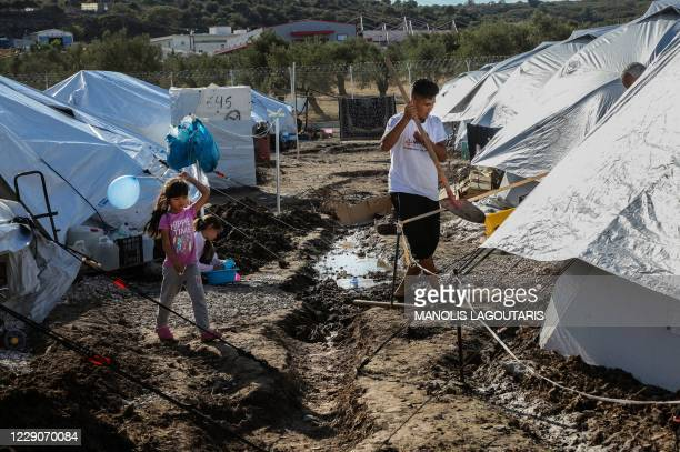Girl holds a airballoon as she walks among tents in the Kara Tepe camp for refugees and migrants on the island of Lesbos on October 14, 2020. -...